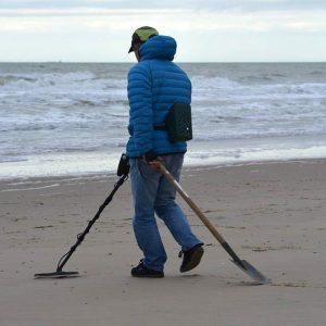 Uomo in spiaggia con metal detector